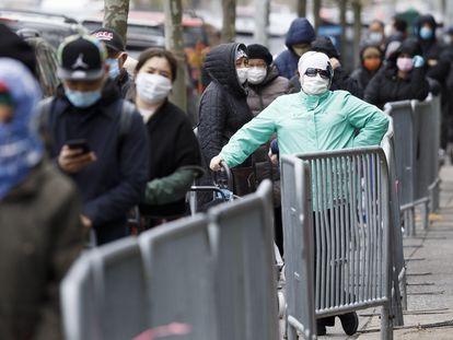 La gente espera en una fila larga para recoger comida en un banco de alimentos en Nueva York, EE. UU.