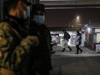 Trabajadores electorales llevan las cajas con los votos, resguardados por el Ejército chileno, este sábado, en Santiago de Chile.