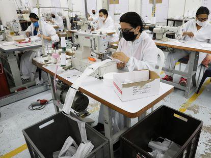 Las trabajadoras de la empresa de ropa infantil en Bogotá (Colombia) fabrican mascarillas, en una imagen del pasado mayo.