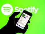 SPAIN - 2021/03/24: In this photo illustration the Spotify app in App Store seen displayed on a smartphone screen and a Spotify logo in the background. (Photo Illustration by Thiago Prudêncio/SOPA Images/LightRocket via Getty Images)