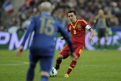 Xavi pasa el balón ante el francés Jallet.