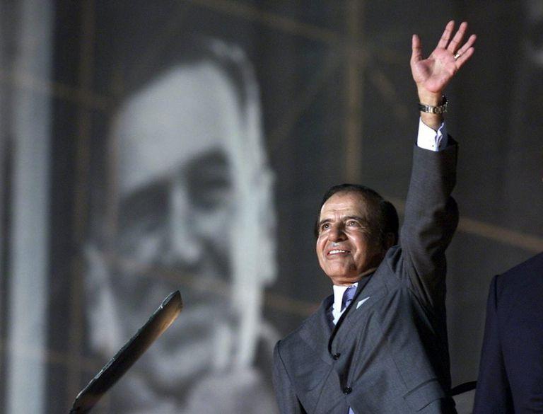 Carlos Menem saluda a sus simpatizantes, con un retrato del extinto presidente argentino Juan Domingo Perón como telón de fondo, en el estadio de River Plate, en abril de 2003.
