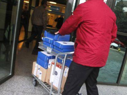 Un hombre transporta un carrito con documentación de una causa judicial y la introduce en los juzgados de Lugo.