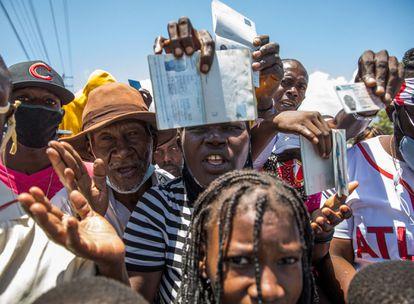 Ciudadanos haitianos muestran sus pasaportes para pedir asilo frente a la embajada de Estados Unidos en Tabarre, este sábado.