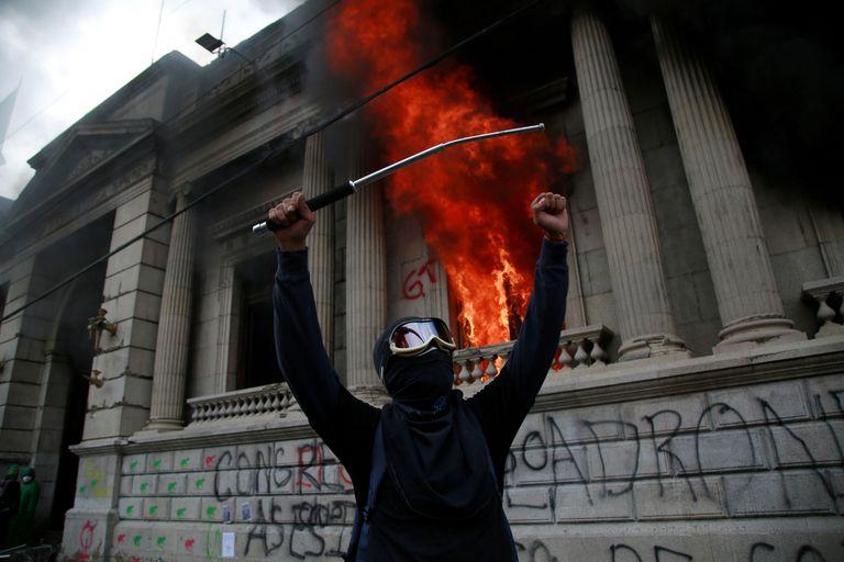 Un hombre protesta frente al Congreso de Guatemala en llamas este sábado.