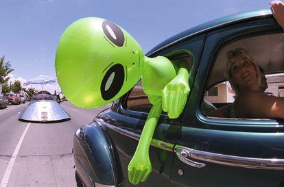 Un muñeco alienígena cuelga de la ventana de un automóvil en el centro de Roswell, Nuevo México, el 1 de julio de 2000 como parte del Festival OVNI anual.