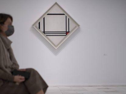 Una mujer sentada frente a una obra de Mondrian.