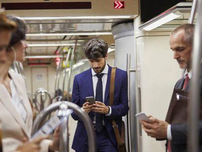 Un grupo de personas utilizando sus teléfonos móviles en un tren de Cercanías.