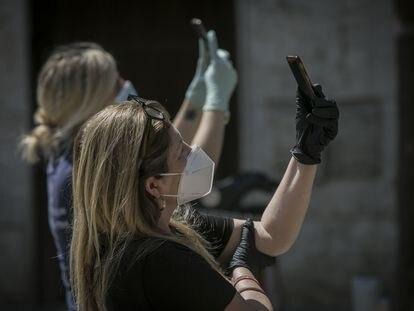 Dos personas protegidas con mascarillas y guantes graban con sus móviles durante el estado de alarma en Sevilla (Andalucía, España).