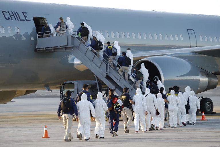 Migrantes venezolanos y colombianos son deportados vestidos con equipo de protección contra la covid-19, en el aeropuerto de Iquique, Chile, este miércoles.