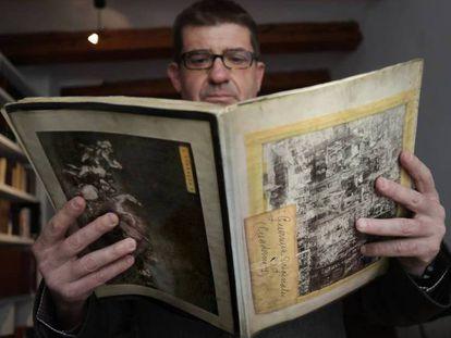 El periodista Javier Monjas, con el cuaderno del fotógrafo Calvache con fotos de Guernica.