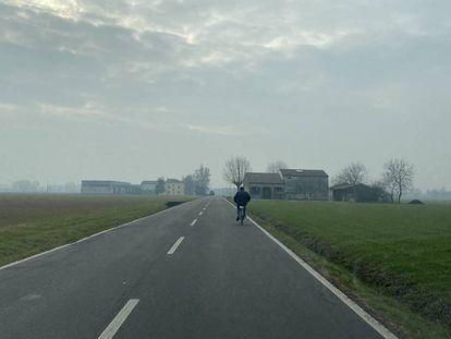 Un agricultor circula en bicicleta poro una carretera cercana a Parma.