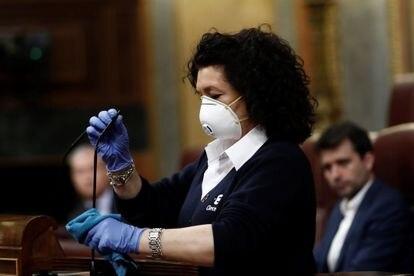 La ujier del Congreso Valentina Cepeda desinfecta el micrófono tras la intervención de cada diputado este miércoles en el pleno.