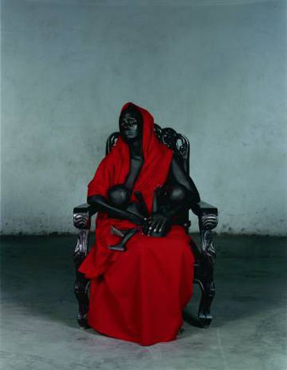 Madonna negra doliente, amamantando dos niños, que asoman entre los pliegues barrocos de su mantel rojo sangre de Vanessa Beecroft.