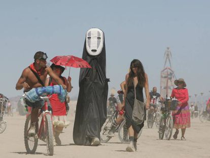 Asistentes al Burning Man caminan por Black Rock Desert.