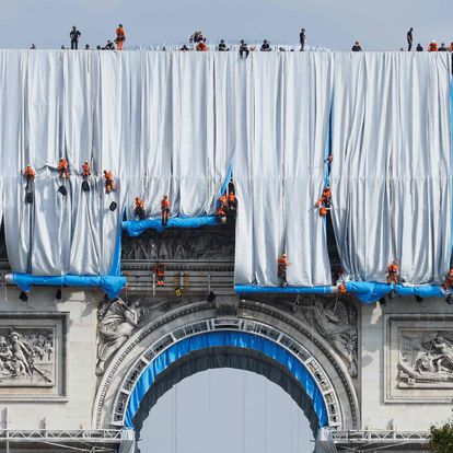 Workers unravel silver blue fabric, part of the process of wrapping L'Arc de Triomphe in Paris on September 12, 2021, designed by late artist Christo. - Work has begun on wrapping the Arc de Triomphe in Paris in silvery-blue fabric as a posthumous tribute to the artist Christo, who had dreamt of the project for decades. Bulgarian-born Christo, a longtime Paris resident, had plans for sheathing the imposing war memorial at the top of the Champs-Elysees while renting an apartment near it in the 1960s. (Photo by Thomas SAMSON / AFP) / RESTRICTED TO EDITORIAL USE - MANDATORY MENTION OF THE ARTIST UPON PUBLICATION - TO ILLUSTRATE THE EVENT AS SPECIFIED IN THE CAPTION