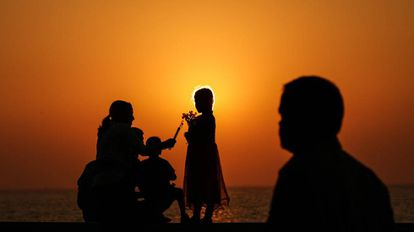 Una familia juega al atardecer en una playa.