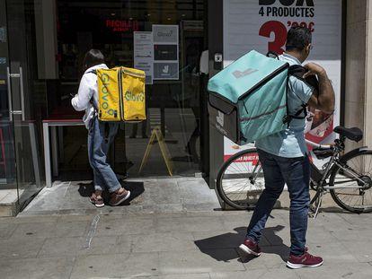 Dos repartidores recogen sus pedidos en un establecimiento de comida rápida en Barcelona.