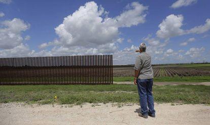 Un hombre señala un tramo de la valla fronteriza incompleta en Brownsville (Texas)