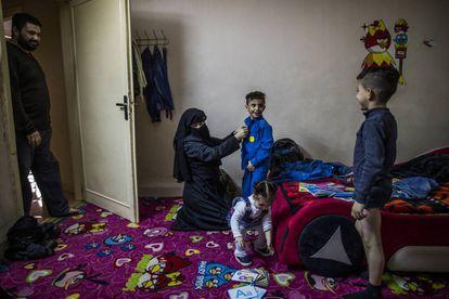 Hanan, la madre, ayuda a vestirse a los niños antes de ir a la escuela ante la atenta mirada del padre, Mohamed.