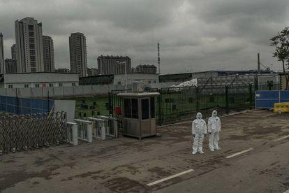 Dos guardias de seguridad con trajes protectores, el 11 de abril a la entrada del hospital Leishenshan, recinto que fue levantado de la nada en 10 días y que acogió en total a 2.011 enfermos en sus 1.500 camas (cerró sus puertas el pasado 15 de abril).