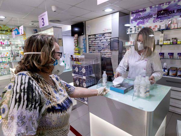 GRAF3320. MURCIA, 20/04/2020.- Una empleada de farmacia de Archena, Murcia, despacha una mascarilla KN95 a una clienta, este lunes, en el vigésimo séptimo día del estado de alarma decretado por el gobierno para frenar la pandemia del COVID 19. EFE/Marcial Guillén
