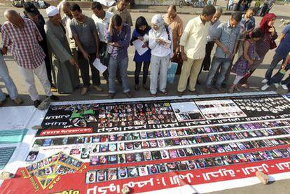 Un grupo de personas observa una pancarta con fotos de los maniefstantes muertos en las protestas de la Plaza Tahrir en enero y febrero.