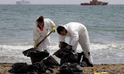 """Operarios de limpieza del Ayuntramiento de Valencia recogen """"galletas"""" de chapapote producidas por un vertido de fuel en la playa de El Saler, en abril de 2014. EFE/"""