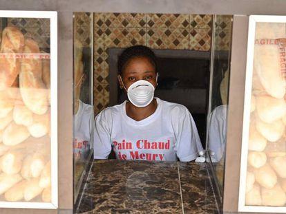 Una mujer luce una mascarilla preventiva frente al coronavirus mientras vende pan cerca de Abiyán.
