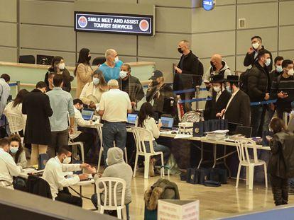 Viajeros recién llegados a Israel esperan a la colocación de pulseras electrónicas de seguimiento, el lunes en el aeropuerto de Tel Aviv.