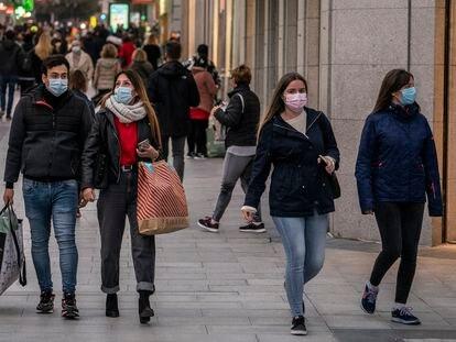 Varias personas con bolsas de diferentes comercios caminan por la calle Preciados, en Madrid, el pasado diciembre.
