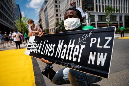 Un hombre sostiene un letrero con el nuevo nombre de la calle 16:  plaza Black Lives Matter.