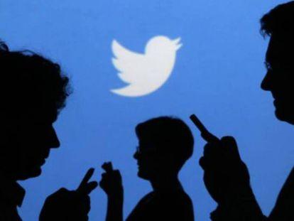 Varias personas que usan sus móviles frente a un cartel de Twitter