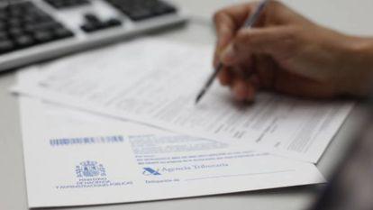 Un contribuyente rellena unos documentos para Hacienda.