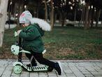 Un niño monta en su patinete por el parque