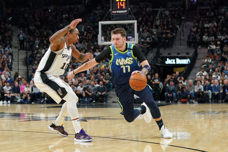 Luka Doncic, jugador de Dallas Mavericks, trata de driblar a DeMar DeRozan, de San Antonio Spurs.