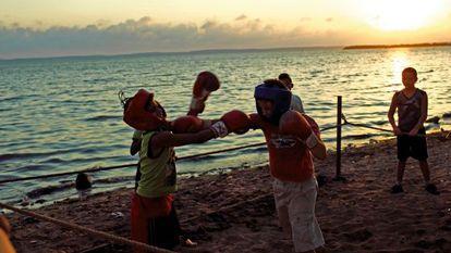 Durante el ocaso en una playa de Cienfuegos, unos muchachos hacen boxeo.