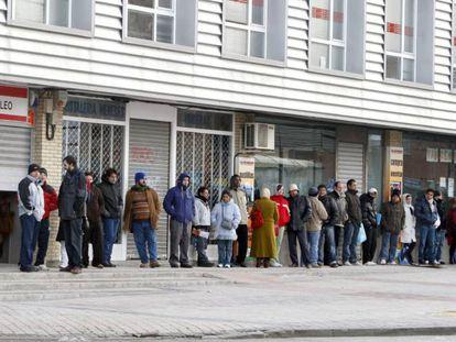 Un grupo de personas espera a la apertura de una oficina del INEM.