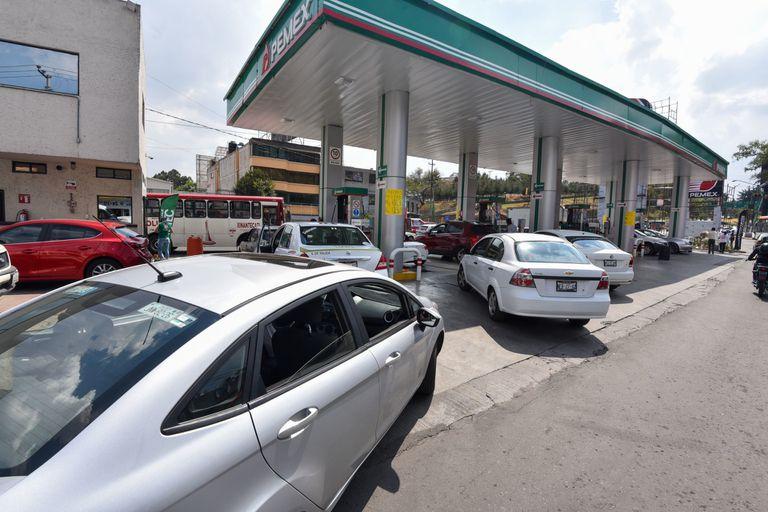Automovilistas hacen fila para poder cargar combustible en México.