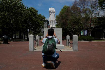 Un hombre toma una fotografía de una estatua de Colón a la que le fue arrancada la cabeza en Boston, en junio de 2020.