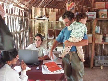 Reyes en su oficina de Yaranda, con su hija en brazos de su compañero Vincent.