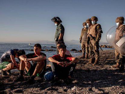 Soldados españoles custodian a un grupo de inmigrantes tras cruzar a Ceuta en la playa del tarajal, en mayo.