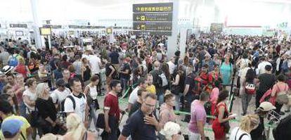Colas de pasajeros para pasar el control de seguridad en el aeropuerto de El Prat, en Barcelona.
