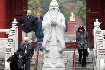 Unos turistas pasean junto a una estatua de Confucio en Pekín.