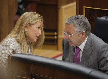 Trinidad Jiménez conversa con el ministro de Fomento, José Blanco, en el Congreso.