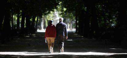 Dos jubilados pasean por el parque del Retiro en Madrid.