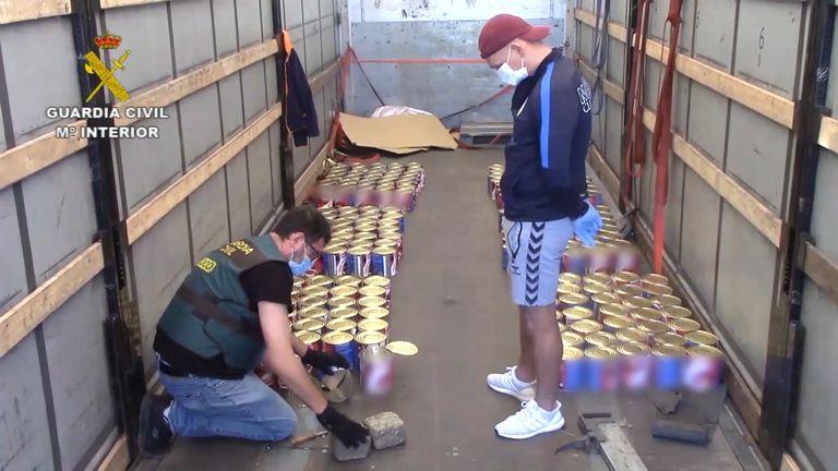Un agente abre latas de tomate llenas de hachís ante la mirada de un narcotraficante.