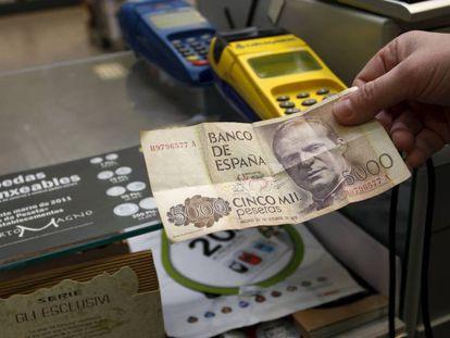 Un comerciante sostiene un billete de 5000 pesetas en un establecimiento.