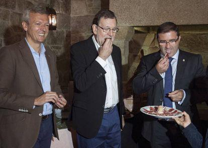 Mariano Rajoy; el vicepresidente de la Xunta, Alfonso Rueda, y el alcalde de A Cañiza (Pontevedra), Miguel Domínguez, degustan una tapa de jamón.