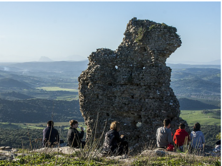 Un grupo de personas observa los restos de la muralla de Lacipo